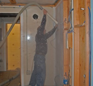 Blowing dense-pack cellulose insulation into the test walls.
